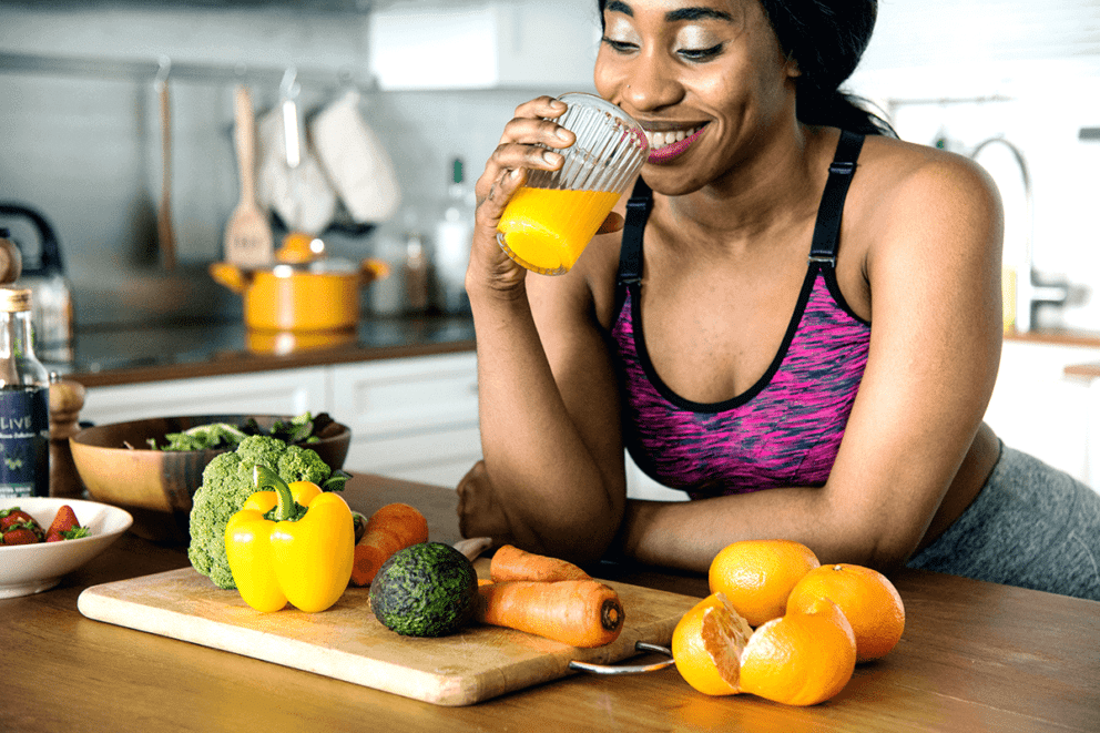 A woman is enjoying a glass of orange juice in her kitchen, dressed in activewear.